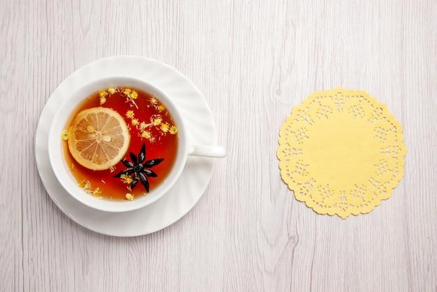 멀리서 바라보는 접시 위의 차 한 잔 가벼운 탁자에 있는 레이스 냅킨 옆 접시에 레몬을 넣은 차 한 잔