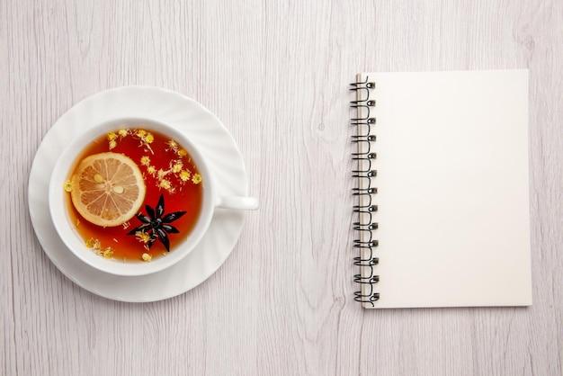 멀리서 바라보는 접시 위에 있는 차 한 잔 밝은 탁자에 있는 흰색 공책 옆에 있는 접시에 레몬을 넣은 차 한 잔