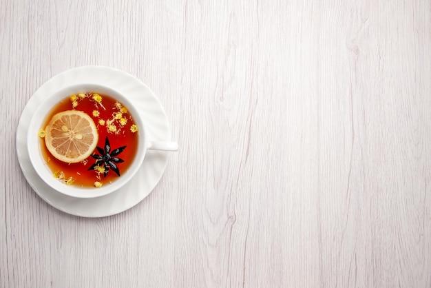 멀리서 보면 접시에 있는 차 한 잔 나무 탁자의 왼쪽에 있는 접시에 레몬을 넣은 차 한 잔