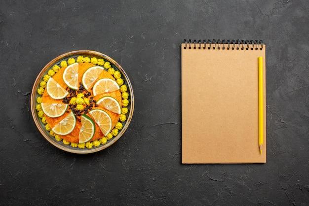 Vista dall'alto da lontano torta appetitosa torta appetitosa con fette d'arancia sul piatto grigio accanto al quaderno crema e matita gialla sul tavolo scuro