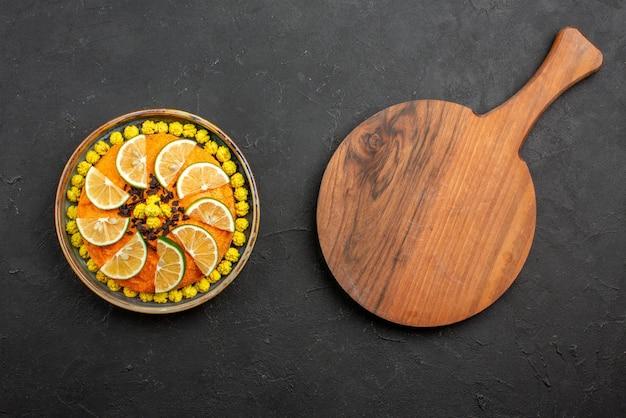 暗いテーブルのまな板の横にある灰色のプレートにオレンジのスライスと遠くの食欲をそそるケーキケーキからの上面図