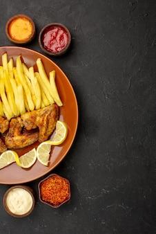 テーブルの上の異なる種類のソースとスパイスの3つのボウルの間の遠くの食欲をそそるチケンチキンウィングフライドポテトとレモンからの上面図