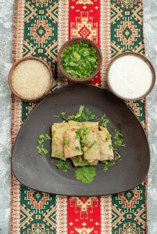 Top view from afar appetizing dish appetizing plate of stuffed cabbage herbs rice sour cream on colored tablecloth with patterns in the center of grey table