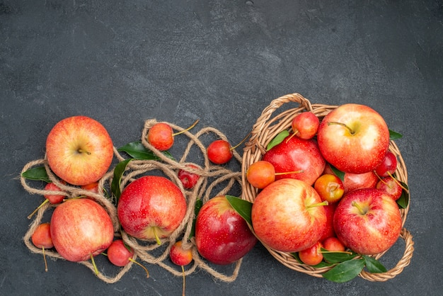 Top view from afar apples the appetizing apples cherries in the basket rope on the dark table