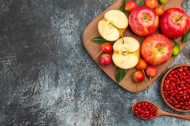 Vista dall'alto da lontano mele mele ciliegie sul tagliere melograno nella ciotola