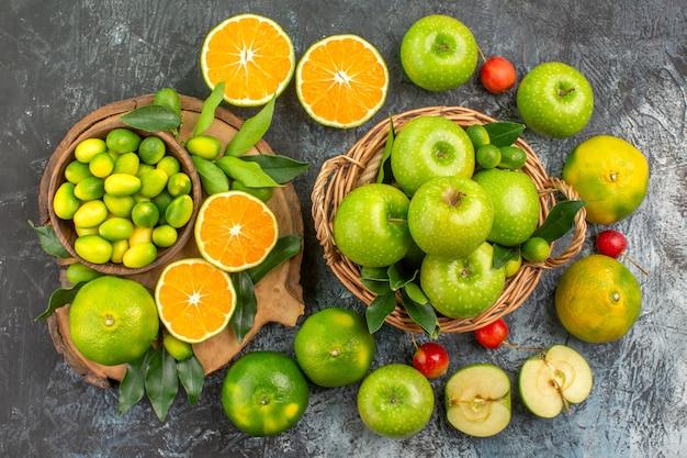 Вид сверху издалека яблоки яблоки в корзине вишни цитрусовые на доске