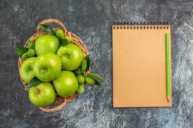 Vista dall'alto da lontano mele cesto di mele verdi con foglie notebook matita
