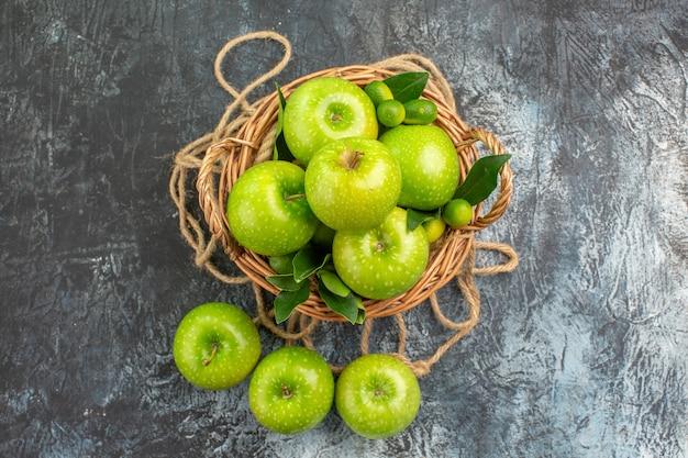 葉の柑橘系の果物のロープで食欲をそそるリンゴの遠くのリンゴバスケットからの上面図