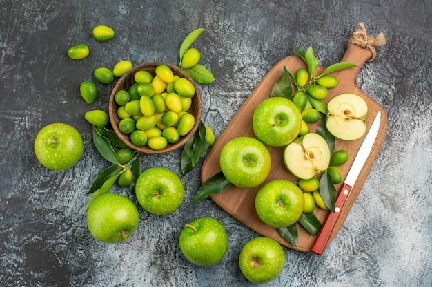 Top view from afar apples board of the appetizing green apples knife citrus fruits