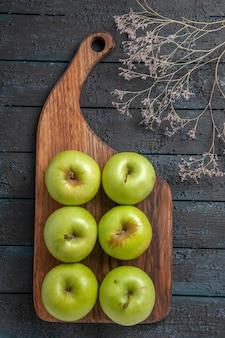 Vista dall'alto da lontano mele a bordo di sei appetitose mele verdi sul tagliere accanto ai rami degli alberi sulla superficie scura