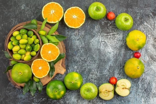 遠くからの上面図リンゴ葉チェリーとボード上の柑橘系の果物