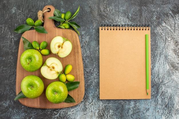 Vista dall'alto da lontano mele mele verdi agrumi sul quaderno crema bordo e matita