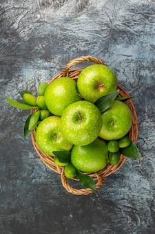 Vista dall'alto da lontano mele mele verdi con foglie nel cestino