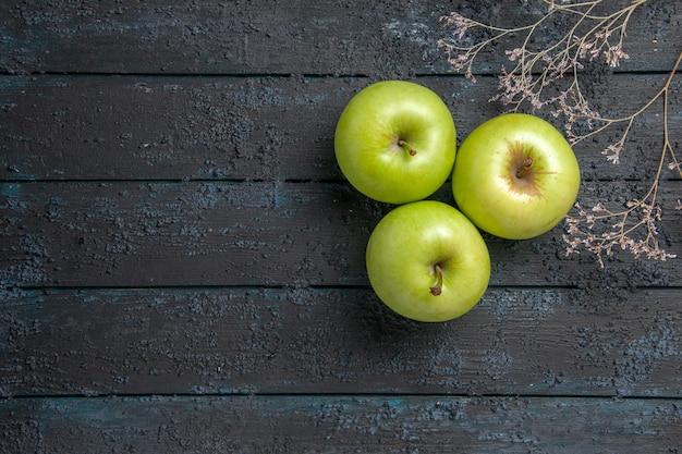 어두운 탁자 오른쪽에 있는 나뭇가지 옆에 있는 3개의 식욕을 돋우는 녹색 사과 테이블에 있는 멀리 있는 사과의 꼭대기