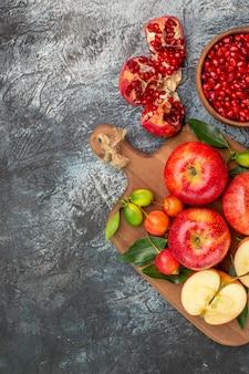 Vista dall'alto da lontano le mele melograno il tagliere con le mele ciliegie