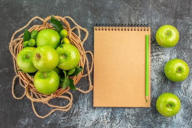 Vista dall'alto da lontano mele cesto di corda di mele con matita taccuino di foglie