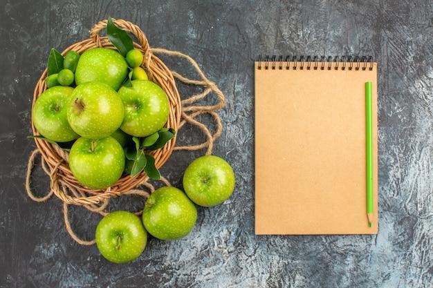 遠くからの上面図リンゴの葉のあるリンゴのロープバスケット柑橘系の果物ノートブック鉛筆