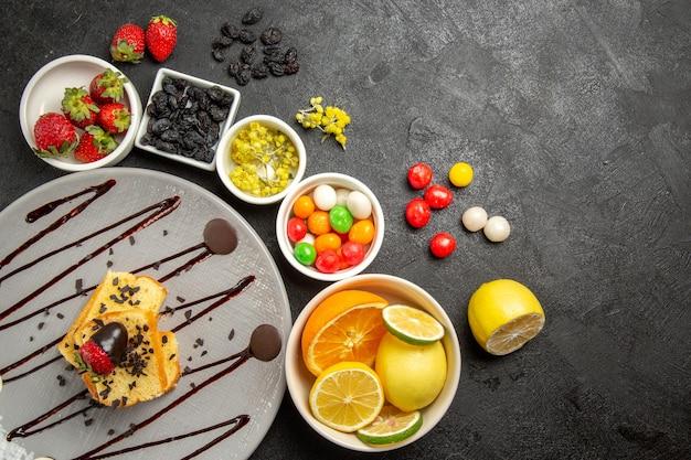하얀색 딸기 라임 레몬 오렌지와 다채로운 과자 옆에 초콜릿으로 덮인 딸기가 있는 멀리 떨어진 딸기와 과일 케이크의 꼭대기 전망