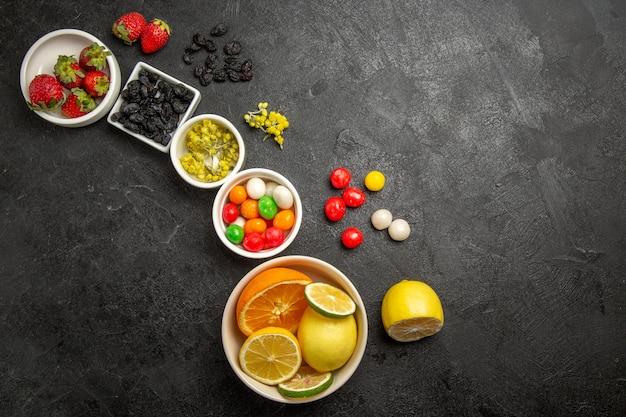 Вид сверху на ягоды и фрукты, белые миски с клубникой, лаймами, лимонами, апельсинами и красочными сладостями на столе