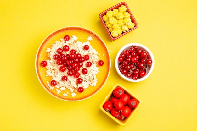 Top view from afar berries bowls of berries appetizing yellow candies oatmeal