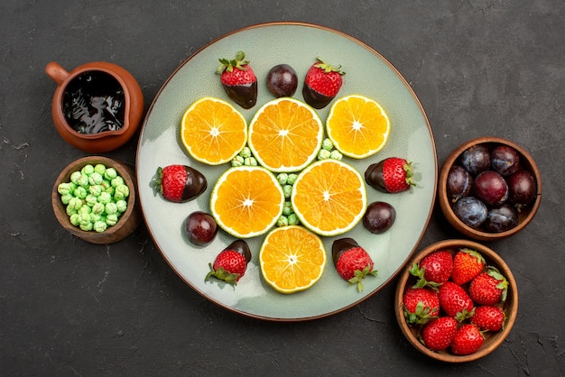 Vista dall'alto da lontano bacche e piatto di cioccolato di arancia tritata e fragole ricoperte di cioccolato accanto alle ciotole con dolci frutti di bosco e salsa al cioccolato