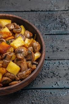 Vista dall'alto da lontano ciotola con cibo ciotola marrone con patate e funghi sul lato sinistro del tavolo