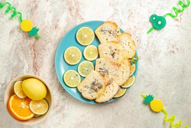 테이블 위의 감귤류 과일 그릇 옆에 있는 파란색 접시에 얇게 썬 레몬을 넣은 맛있는 케이크 조각과 감귤류 과일의 꼭대기 전망