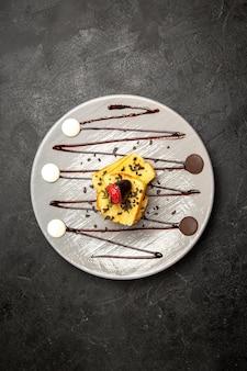 暗いテーブルの灰色のプレートにチョコレートで覆われたイチゴとチョコレートソースと遠くのケーキ食欲をそそるケーキからの上面図