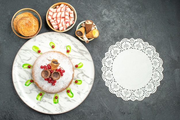 Top view from afar a cake a cake with waffles red currants green sauce bowls of sweets lace doily