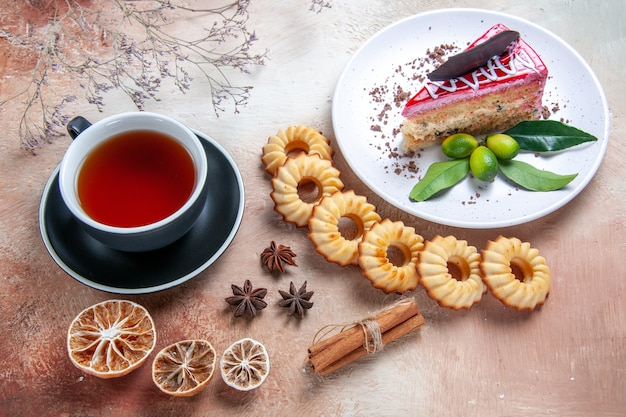 Top view from afar a cake plate of an appetizing cake cookies a cup of tea star anise lemon