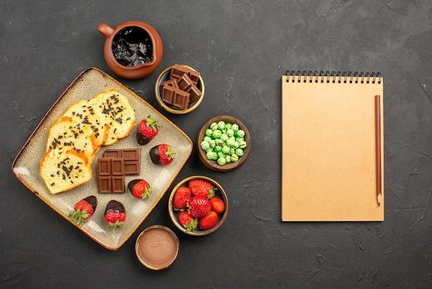 Vista dall'alto da lontano torta e fragole ciotole di cioccolato fragole caramelle verdi e crema al cioccolato accanto al piatto di torta e quaderno con matita