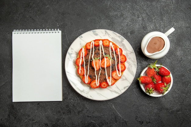 딸기 흰색 노트북 그릇과 테이블에 딸기와 초콜릿이 있는 초콜릿 크림 케이크가 있는 멀리 있는 케이크의 꼭대기