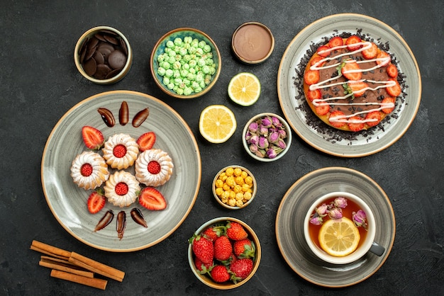 Top view from afar cake with sweets cake with chocolate and strawberry black tea lemons plate of cookies with strawberry bowls of chocolate and different sweets on black table