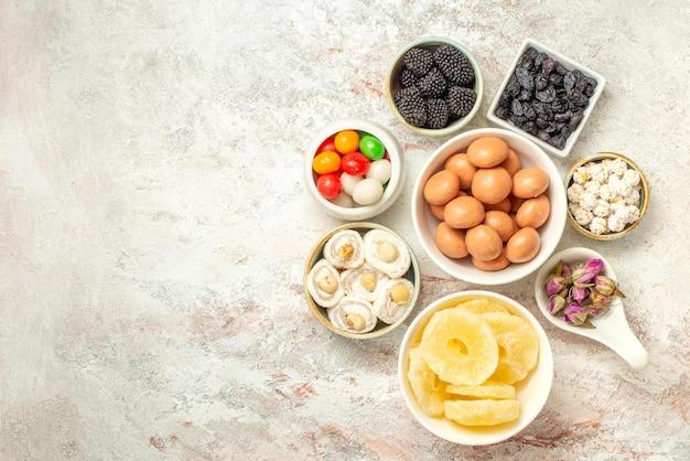 Vista dall'alto da lontano caramelle in ciotole caramelle appetitose e ananas essiccati in ciotole sul tavolo luminoso