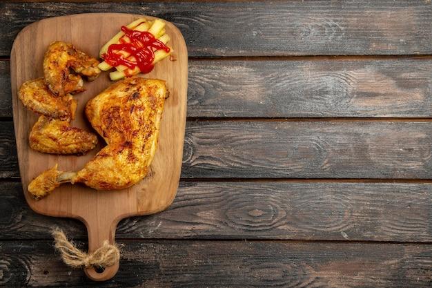 暗いテーブルの左側にある木製のまな板の上で、遠くの鶏肉の食欲をそそるフライドポテトチキンとケチャップからの上面図