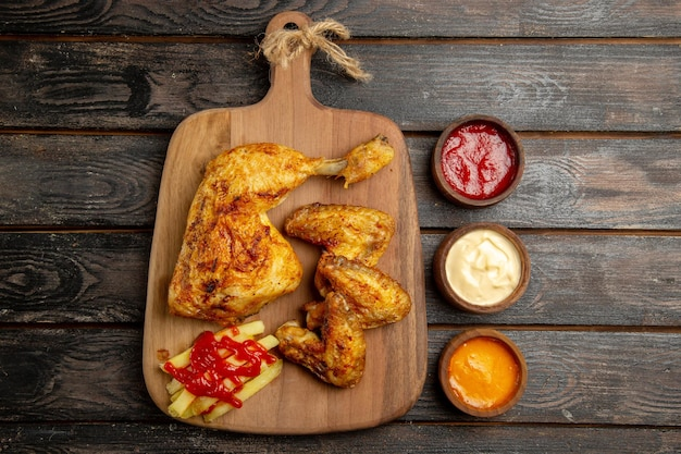 Top view from afar chicken appetizing french fries chicken and ketchup on the wooden cutting board next to bowls of colorful sauces on the dark table