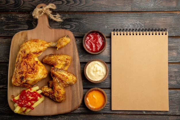 Top view from afar chicken cream notebook appetizing french fries chicken and ketchup on the wooden cutting board next to bowls of colorful sauces on the dark table
