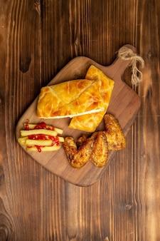 Vista dall'alto da lontano pollo e torta ali di pollo torta e patatine fritte con ketchup sul tagliere