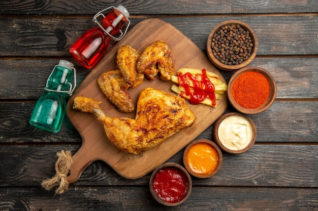 검은 후추 소스 향신료의 커팅 보드 그릇에 감자 튀김과 케첩을 곁들인 치킨 옆에 있는 멀리 있는 치킨 빨간색과 파란색 병에서 상위 뷰 무료 사진