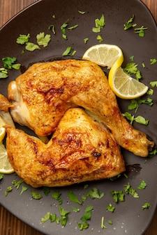 テーブル中央のプレートにハーブとレモンを添えた食欲をそそる鶏肉とレモンを添えた遠方の鶏肉からの上面図