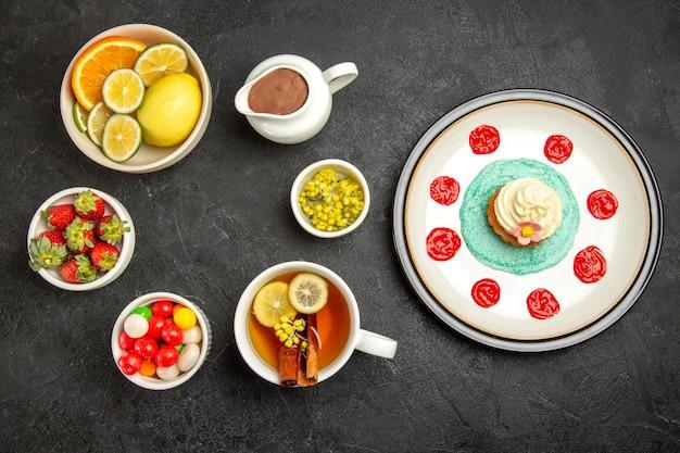 Вид сверху аппетитный кекс с шоколадом и лимоном на тарелке рядом с шоколадными конфетами и лимонами в мисках и чашкой чая с корицей и лимоном