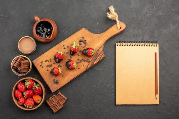 遠くからの上面図チョコレートイチゴボウルにチョコレートクリームとイチゴ、ノートと鉛筆の横にあるキッチンまな板にチョコレートで覆われたイチゴ