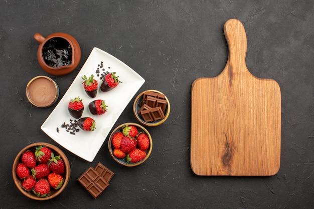 木製のまな板の横にチョコレートクリームとイチゴチョコレートで覆われたイチゴチョコレートと遠くのチョコレートイチゴキッチンボードからの上面図
