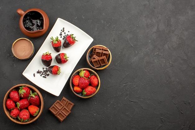 Vista dall'alto da lontano tavola da cucina con fragole al cioccolato con crema al cioccolato e fragole fragole ricoperte di cioccolato cioccolato sul lato sinistro del tavolo
