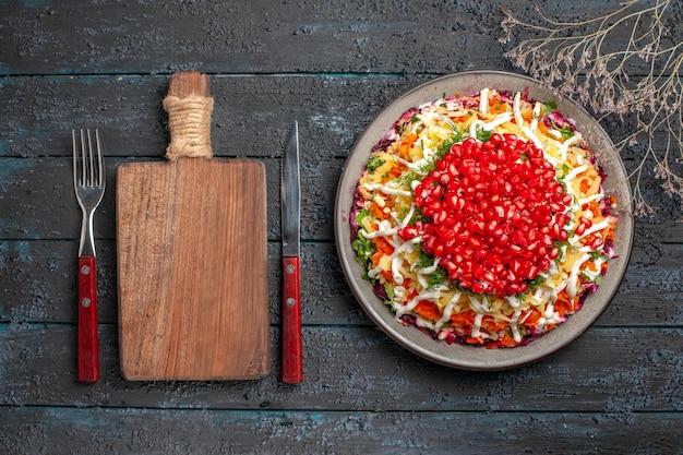 Vista dall'alto da lontano piatto natalizio piatto natalizio con semi di melograno accanto al tagliere di legno forchetta e coltello rami di albero sul tavolo scuro