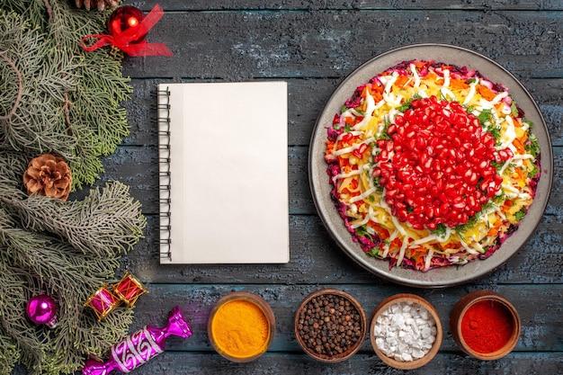 遠くからの上面図クリスマスフードザクロのスパイスボウルと白いノートとトウヒの枝とクリスマスツリーのおもちゃのクリスマス料理