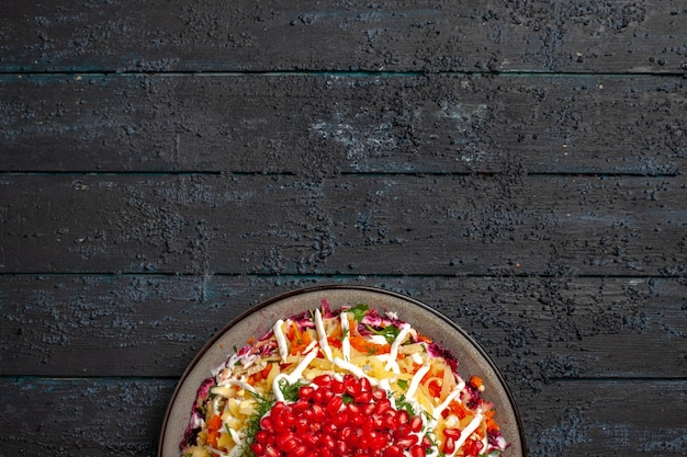 Vista dall'alto da lontano cibo natalizio piatto natalizio con melograno nel piatto sullo sfondo scuro