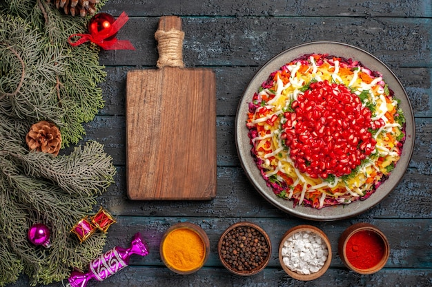 Top view from afar christmas food christmas dish with pomegranatecutting board bowls of spices and spruce branches with christmas tree toys