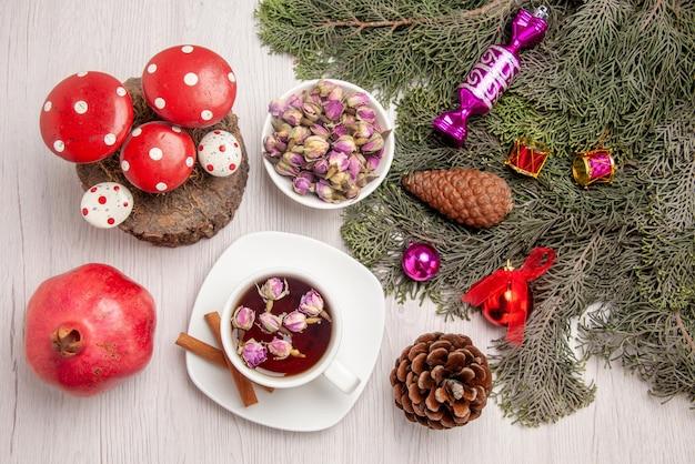 遠くからの上面図クリスマスツリーのおもちゃテーブルの上のコーンとクリスマスツリーのおもちゃとザクロのトウヒの枝の横にある白い受け皿にハーブティーとシナモンのカップ