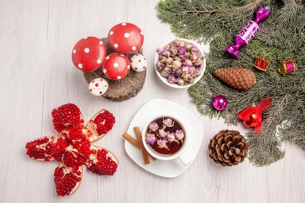 遠くからの上面図クリスマスツリーのおもちゃとテーブルの上の丸いザクロとトウヒの枝の横にある白い受け皿にハーブティーとシナモンのカップ